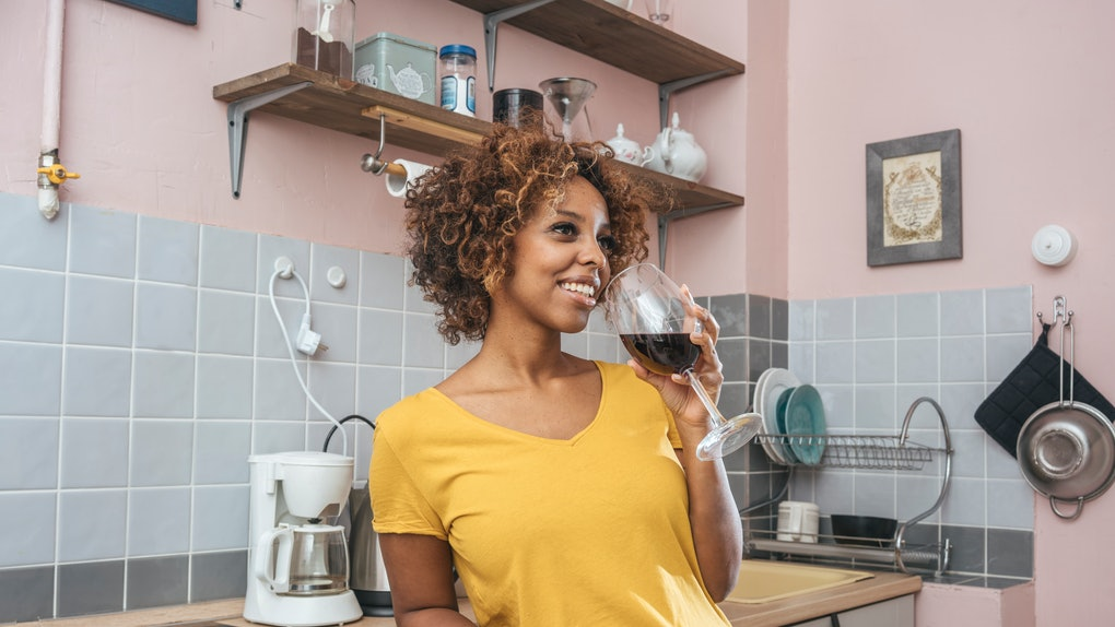 A young woman stands in her pink kitchen and drinks a glass of wine.