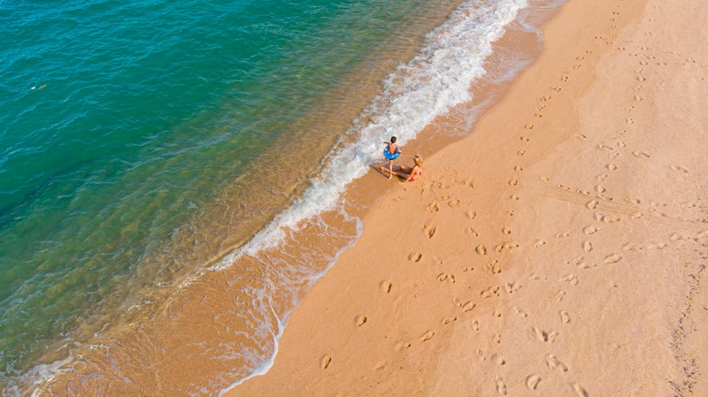Two kids playing on an empty beach. How To Safely Go To The Beach During The Coronavirus Pandemic, According To An Expert