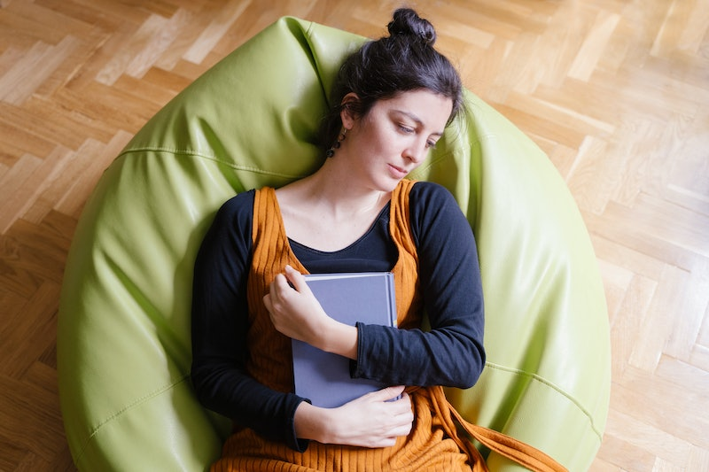 Woman asleep on a beanbag chair clutching a book. If your energy levels are low during the coronavirus pandemic, experts explain how to boost your energy levels.