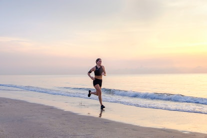 A woman jogs on the beach in the early morning.How To Safely Go To The Beach During The Coronavirus Pandemic, According To An Expert