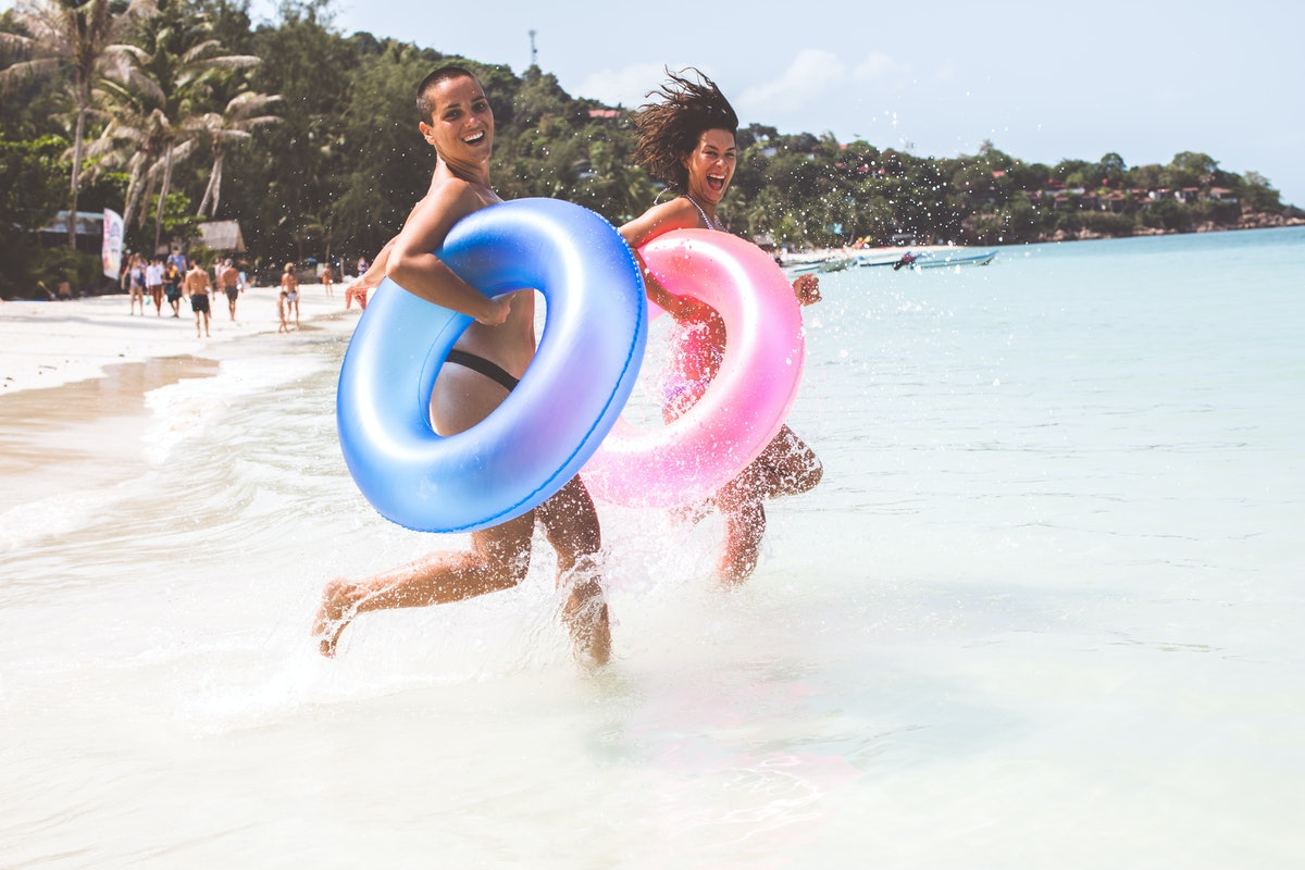 A young lesbian couples runs into the ocean with colorful tube floats in their hands.