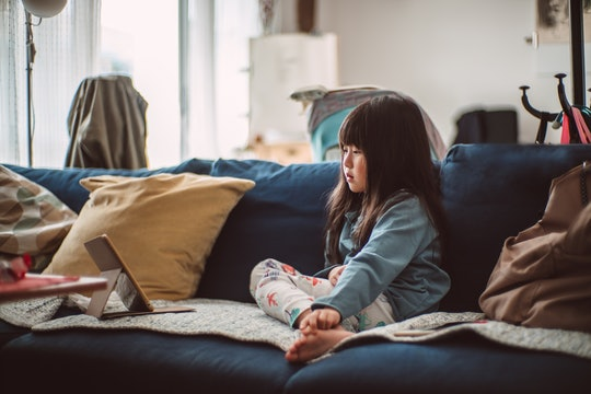 little girl sitting on couch looking at a kindle