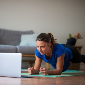 A person holds a plank in her living room while keeping an eye on the yoga class on her laptop. Taking donation-based virtual fitness classes can help support small, locally-owned gyms during the pandemic.