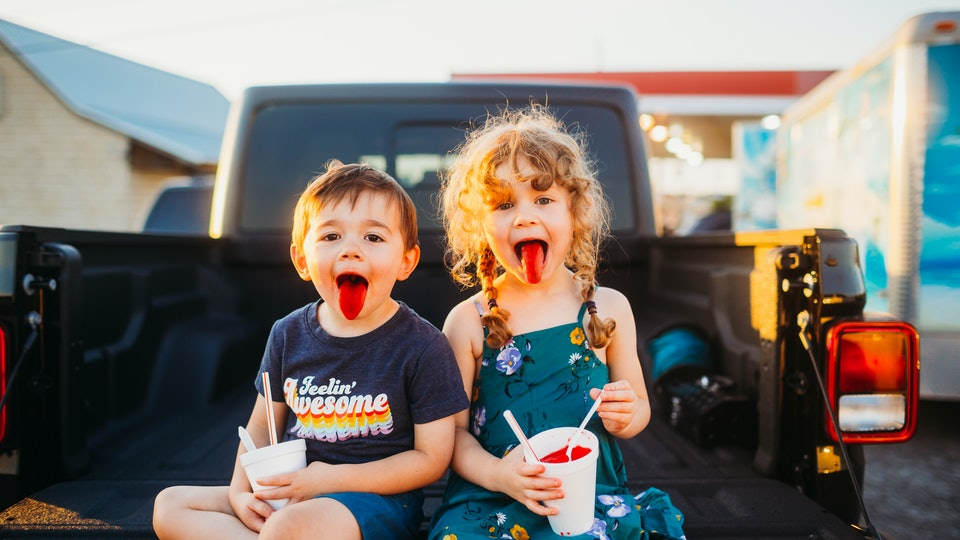kids drinking slush puppies on the back of a pickup truck