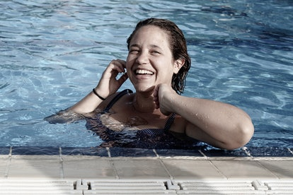 A person smiles at the edge of a pool. Swimming in the ocean might be the safest option for swimming this summer.