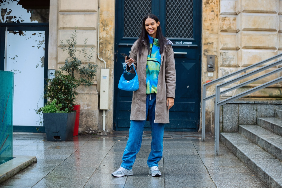 A young woman stands outside on a rainy street in the city in a tie-dye sweatshirt and jeans.