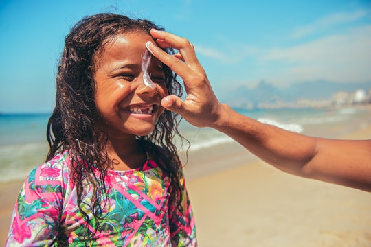 parent putting sunblock on girl's face at beach