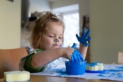toddler girl making paint handprints