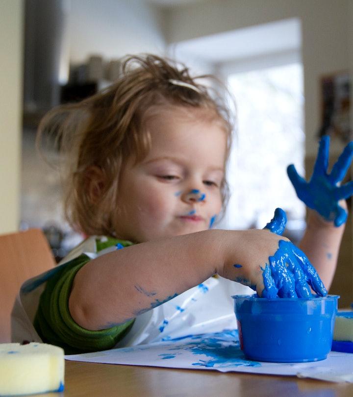 toddler girl making paint handprints