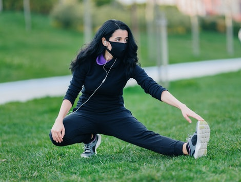 A person stretches her hamstring while wearing a mask in a public park. Public parks are starting to open again, and an expert says it should be fairly safe if you practice social distancing.