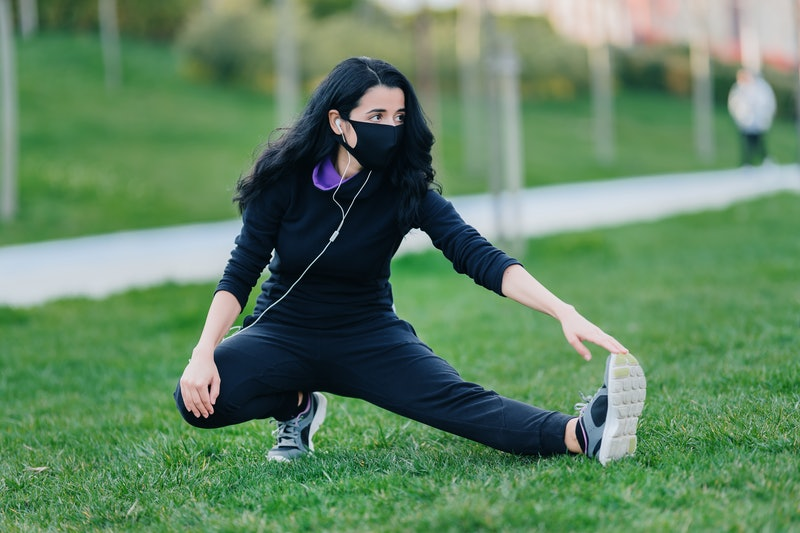 A person stretches her hamstring while wearing a mask in a public park. Public parks are starting to...