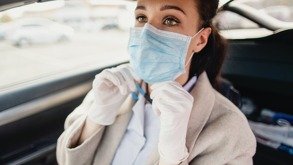 woman putting on face mask in car