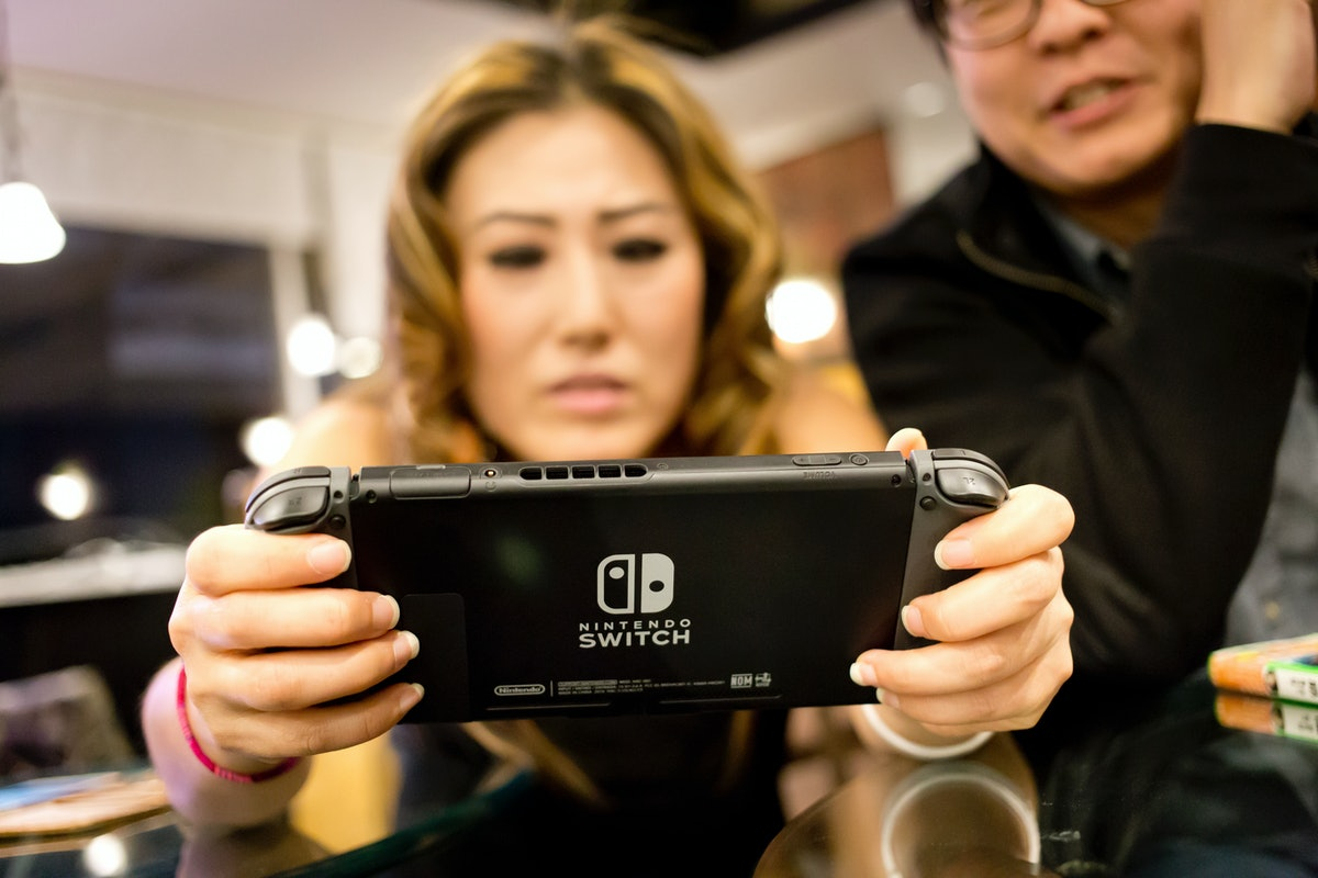 A woman intensely plays animal crossing on her Nintendo Switch.