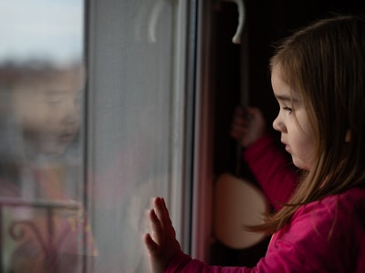 little girl in quarantine looking out window