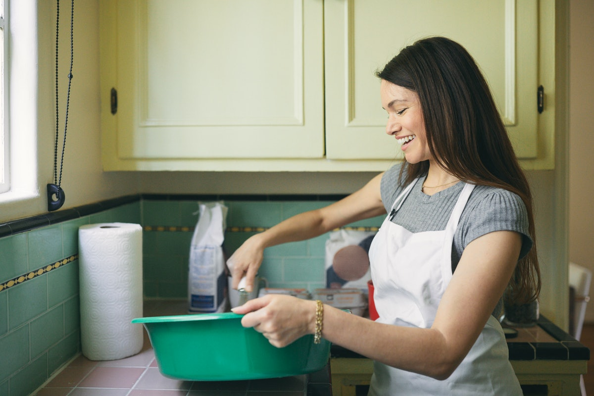 A young woman mixes a cookie dough bread batter in a large, teal bowl in her kitchen.