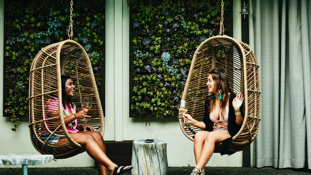 Two friends sit in swinging chairs and drink wine on a summer day.