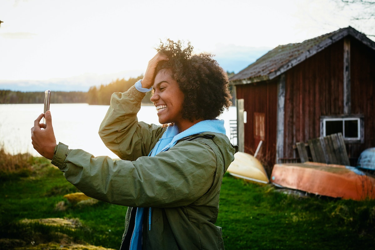 A young woman takes a selfie on her phone while standing next to a rustic home near a lake.