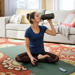 A woman drinks a large nalgene while doing yoga in her living room. Experts explain reasons you're still dehydrated after drinking lots of water.