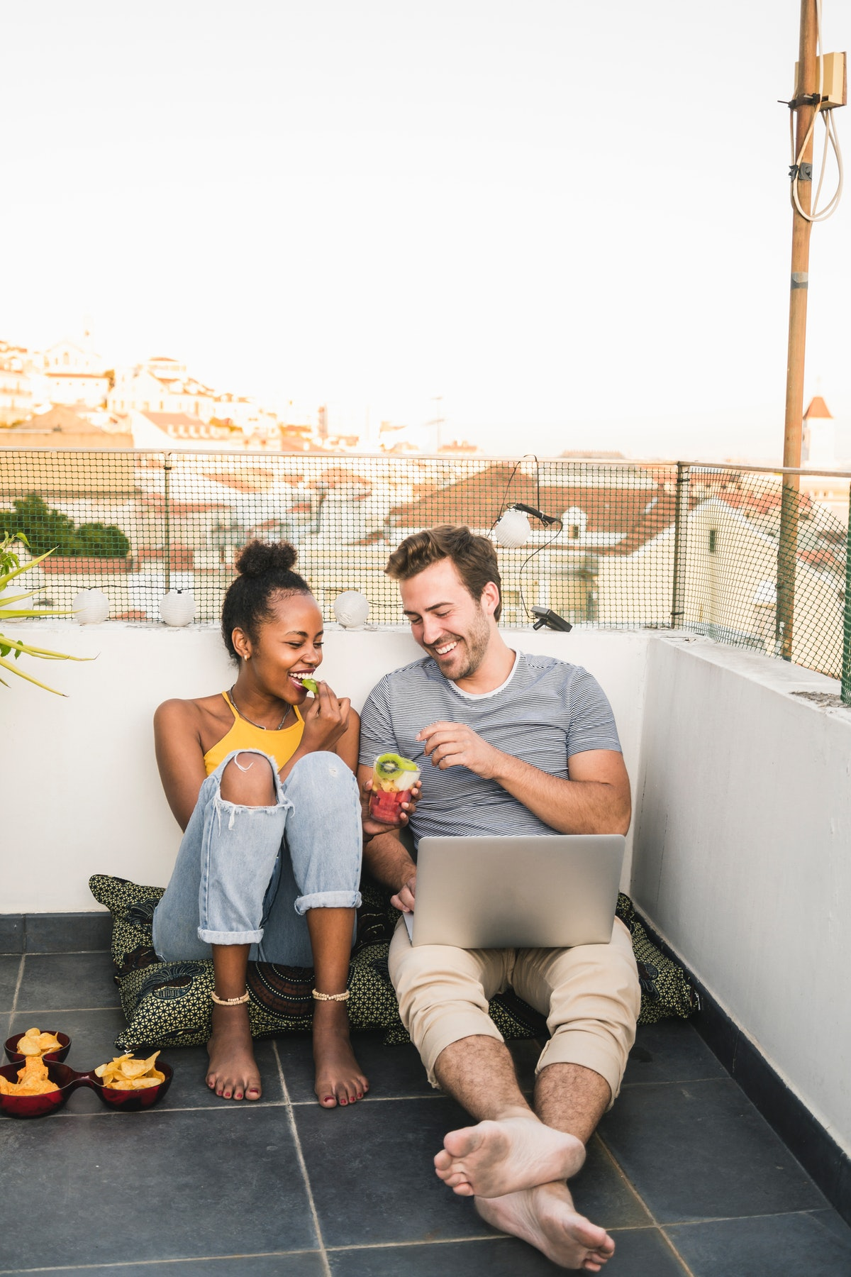 A young couple enjoys snacks and drinks on their rooftop while video chatting.