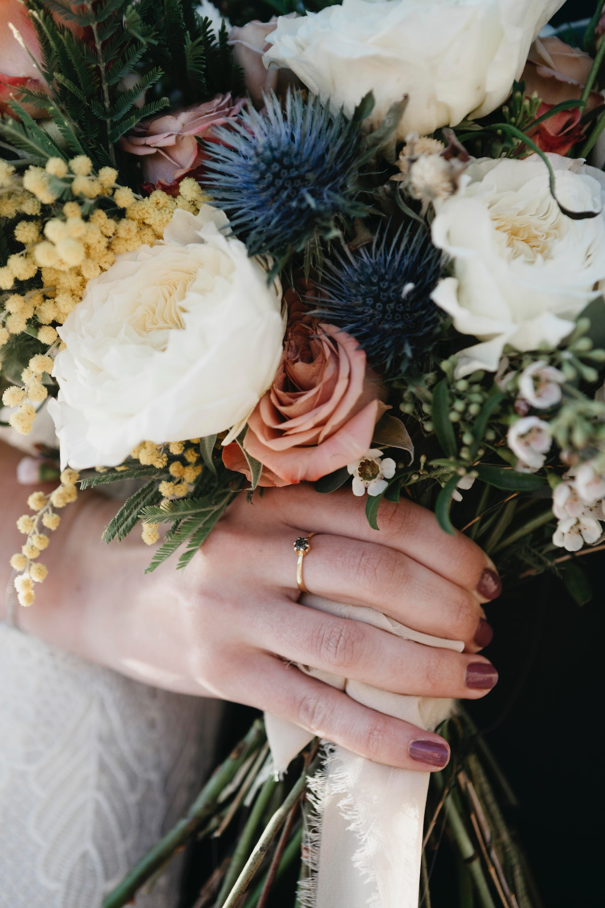 A bride holds a beautiful bouquet of wildflowers on her wedding day.