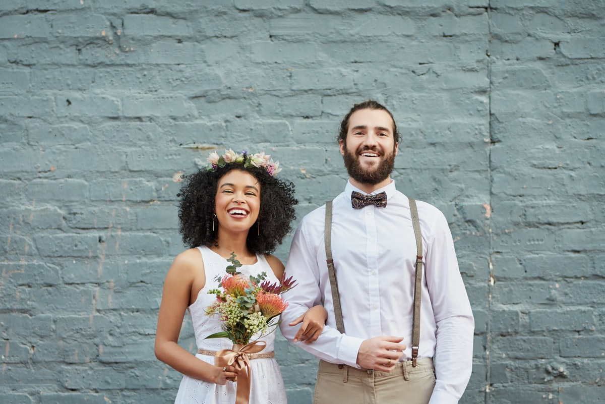 A young couple stands in front of a light blue brick wall on their wedding day.