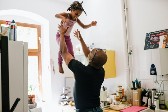 dad tossing his daughter up in the air in the kitchen