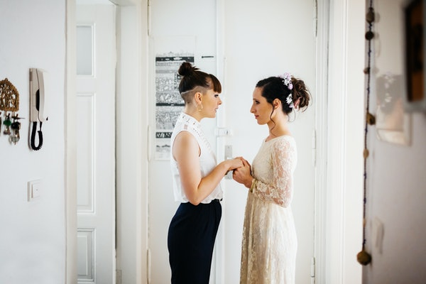 A young lesbian couple stands in a doorway in their home, and recites their vows.