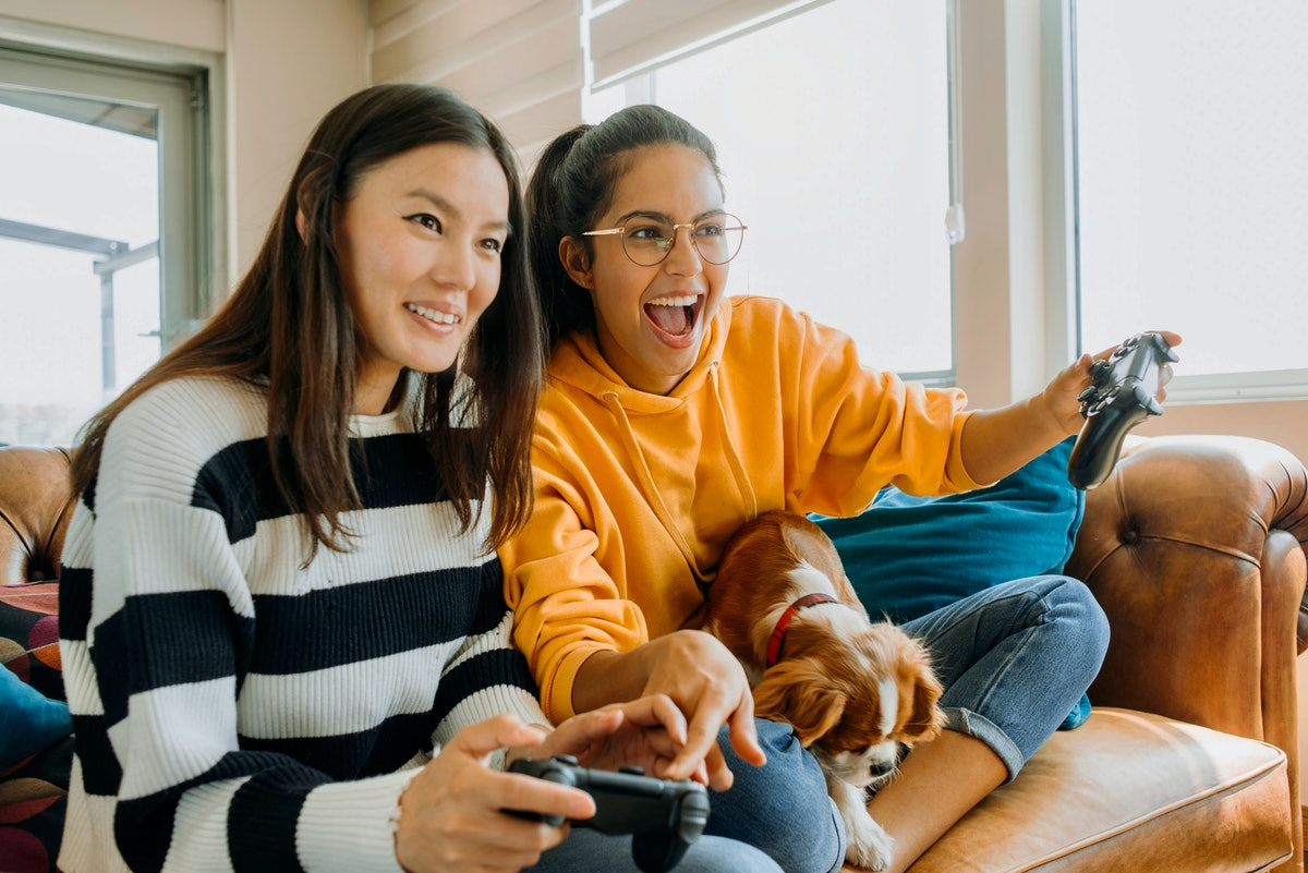 Two friends sit on the couch with their dog and play video games on a sunny afternoon.