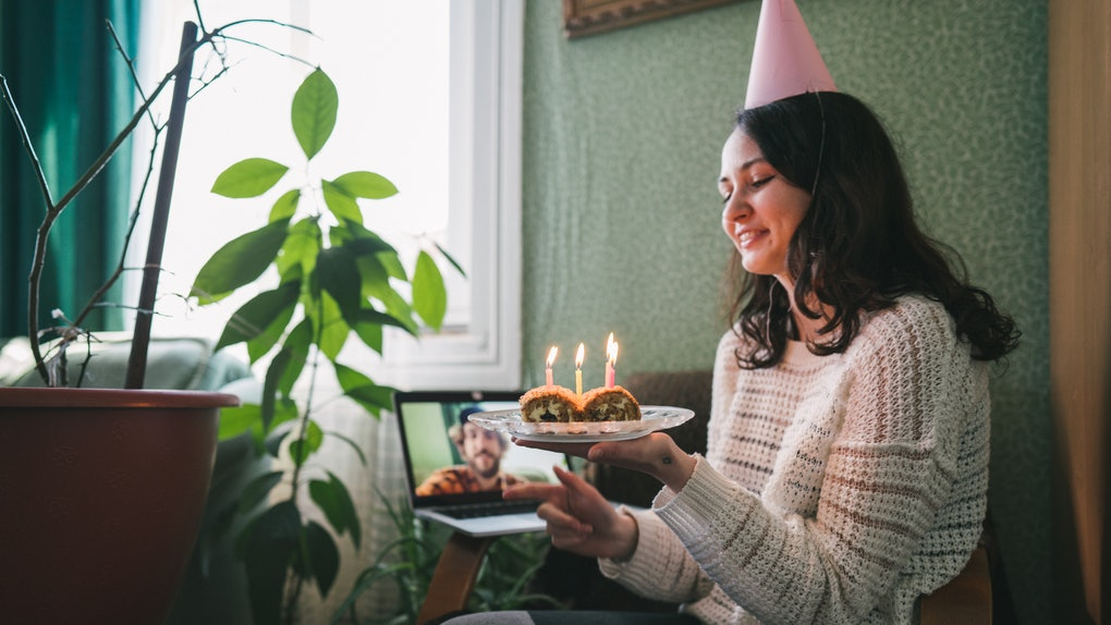 A young woman sits in a chair with a party hat on and a dessert with candles in her hand, and video chats on her laptop.
