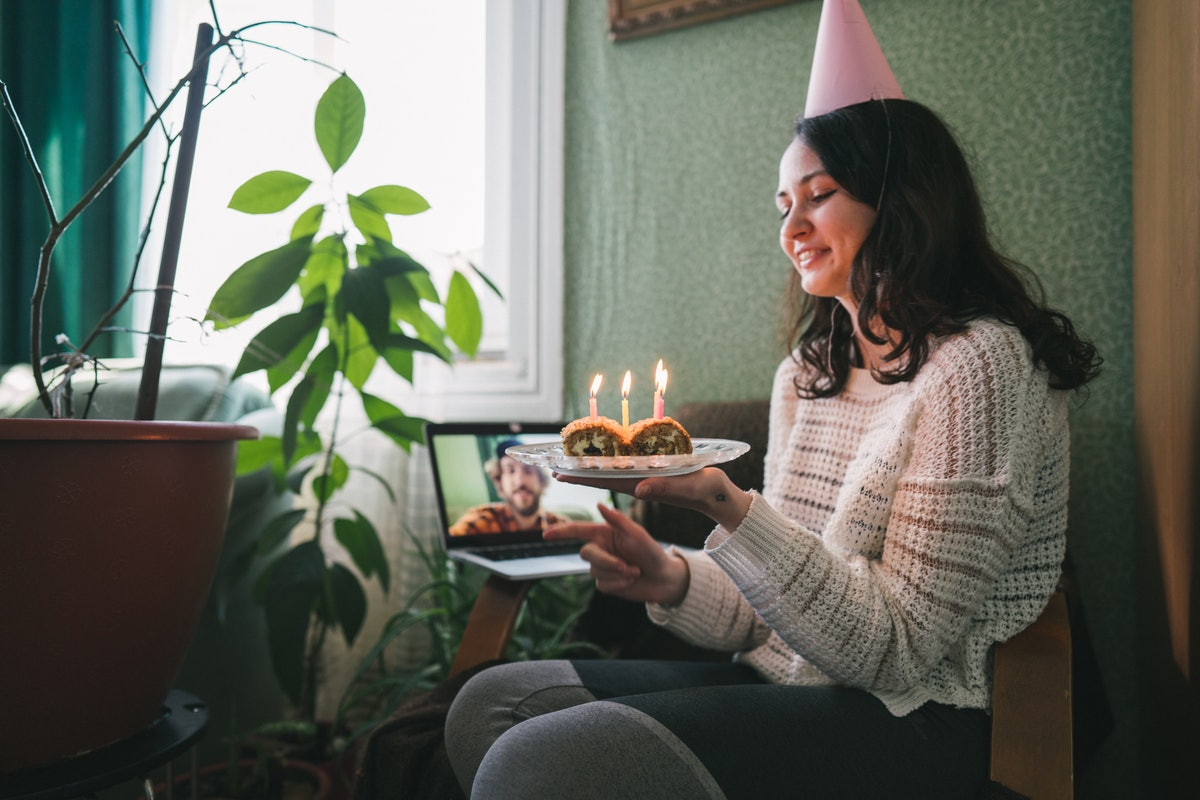 A young woman sits in a chair with a party hat on and a dessert with candles in her hand, and video ...