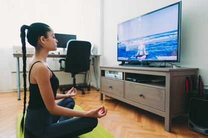 A person sits on their yoga mat and meditates in front of a yoga video on their television. Exercising in front of your roommate can be a very vulnerable experience.