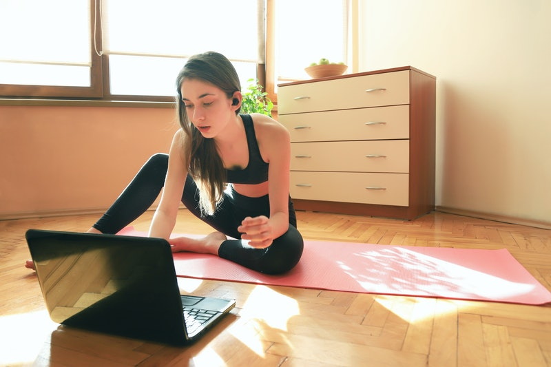 A person sits on their yoga mat and looks at their laptop to choose a workout video. Working out in front of your roommate can feel embarrassing, but that doesn't make exercising at home impossible.