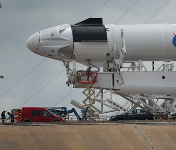 Workers prepare the SpaceX Falcon 9 rocket with the Crew Dragon spacecraft attached for tomorrow's scheduled liftoff from launch pad 39A at the Kennedy Space Center on May 26, 2020 in Cape Canaveral, Florida. NASA astronauts Bob Behnken and Doug Hurley will be aboard the May 27th inaugural flight and will be the first people since the end of the Space Shuttle program in 2011 to be launched into space from the United States.