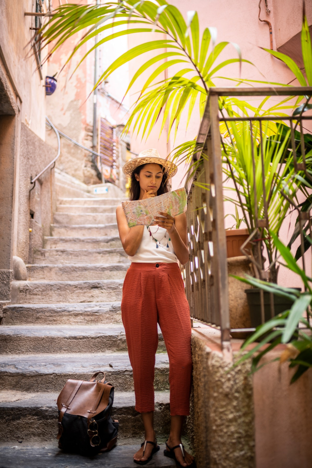 A young woman looks at a map while traveling in Cinque Terre, Italy.