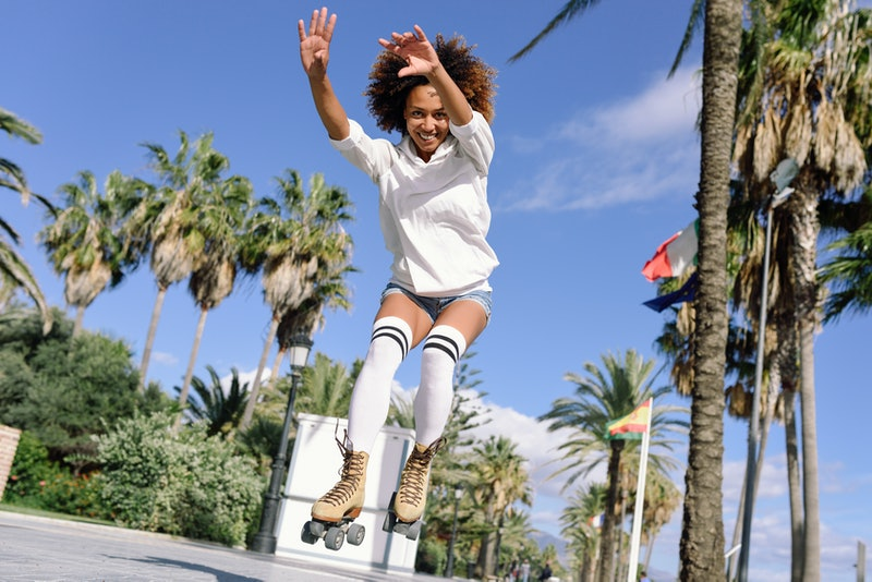 A person jumps in a pair of roller skates. Roller skating can be a good workout if you do it safely, a personal trainer says.