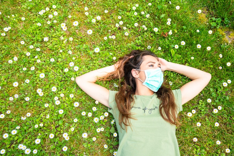 A woman lies in a field of flowers wearing a face mask. Face masks can affect your brain in different ways.