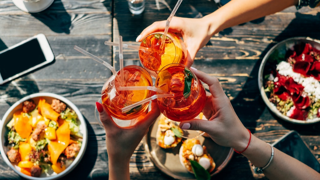 A group of friends toasts with glasses of Aperol Spritz, while eating a colorful meal in the summertime.