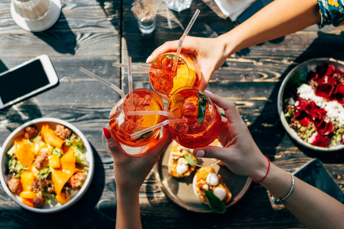 A group of friends toasts with glasses of Aperol Spritz, while eating a colorful meal in the summert...