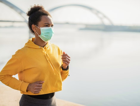 A person wearing a yellow sweatshirt runs along a waterfront while wearing a mask. Virtual events can actually make jogging on Global Running Day more accessible for people of all levels and abilities.
