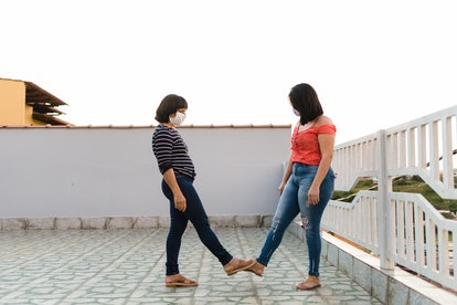 Friends wearing face masks touch toes. If somebody breaks the rules of your isolation bubble, kicking them out can be hard.