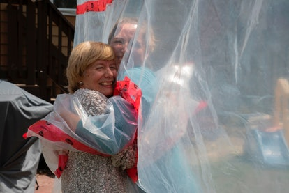 A socially distanced hug through plastic barriers is one way people are fulfilling the need to get the hugs they miss.