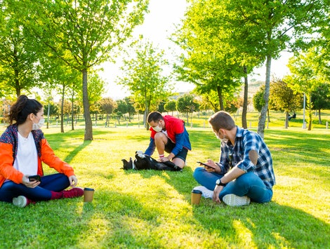 Friends play with their dog in a park. Isolation bubbles of friends or family can be a great way to get through coronavirus - but people who violate rules can make them hard.