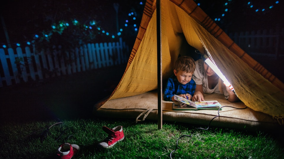 mom and boy camping in backyard tent