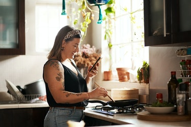 A young woman stands in her kitchen and mixes ingredients in a pan while holding her phone.