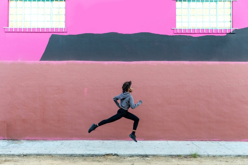 A woman runs in front of a pink building. These free running apps will help you train for a 10k, or just track your progress.