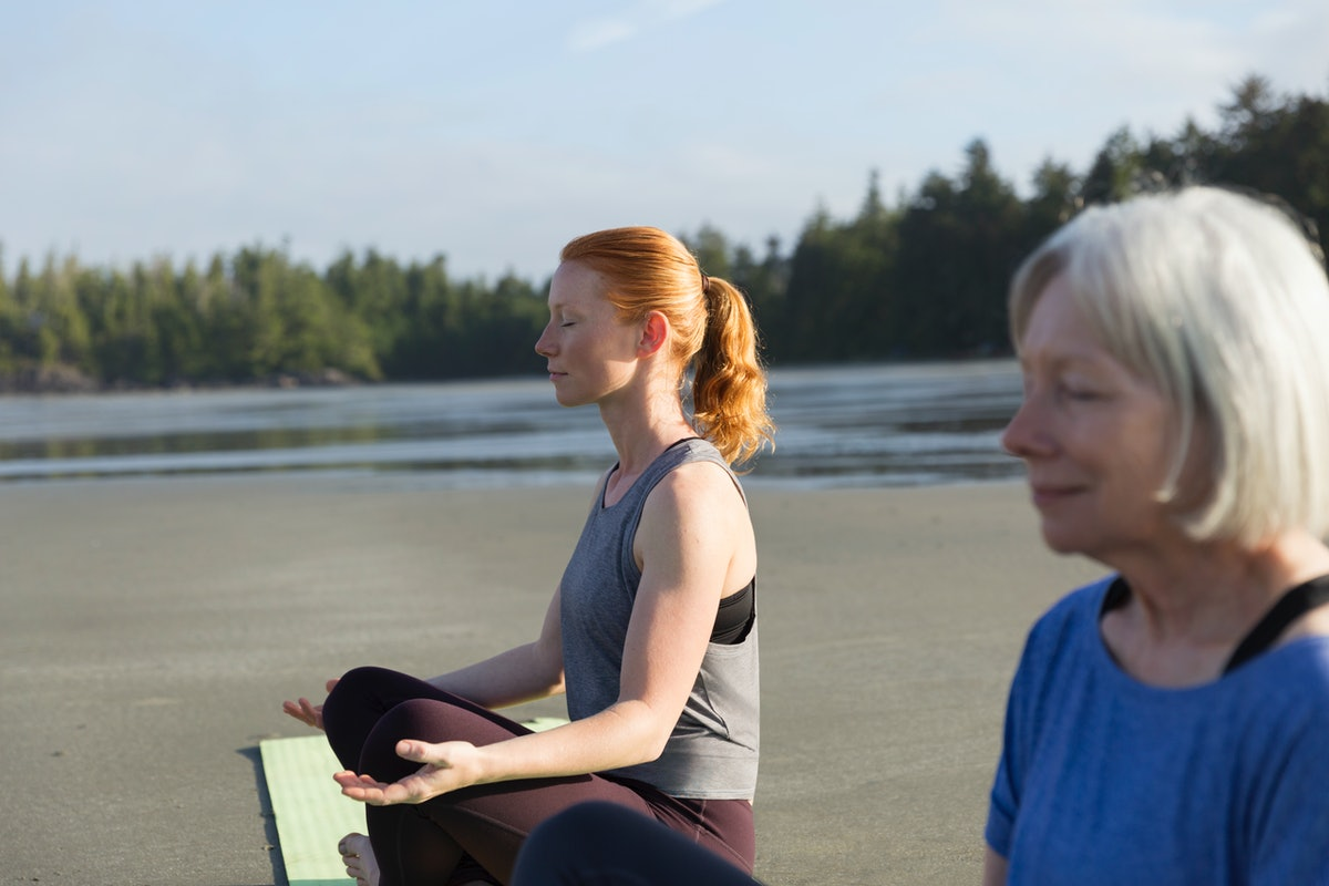 A mother and daughter sit cross-legged on their yoga mats on the beach.