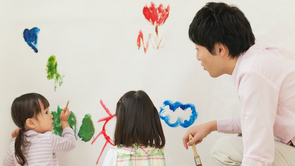 family painting mural on wall