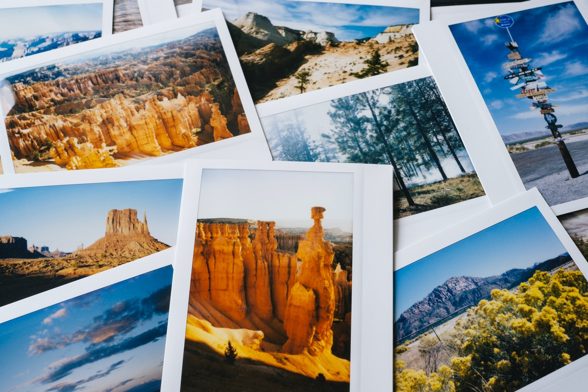 A bunch of Polaroid pictures from a trip are laid out on a table.