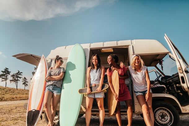 A group of friends laughs outside of a camper on the beach, while holding surfboards and skateboards.