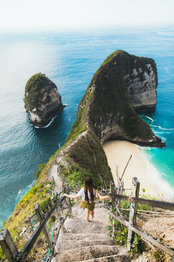 A young woman walks down the stairs on a mountain near the beach in Bali.